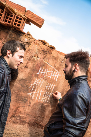 markings: Two guys couning days with chalk markings on a wall Stock Photo