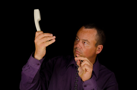 bewildered: Man trying to connect a telephone with a bewildered look on his face