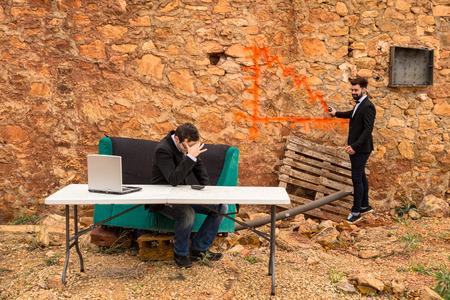 bearish: A bearish chart being drawn with graffiti on a ruin wall, a financial crisis concept Stock Photo