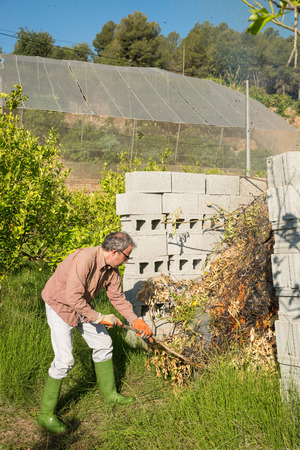Agricultural worker setting fire to pruned branches inside a burner made of concrete blocks photo
