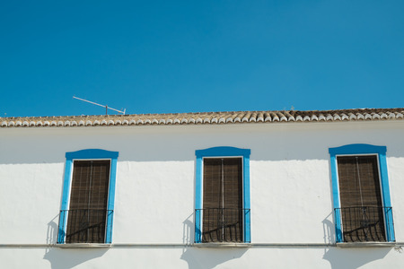 blinded: Detail of a whitewashed Andalusian facade with blinded windows Stock Photo