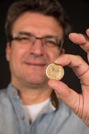 greek coins: Man holding a 100 Greek drachma coin Stock Photo