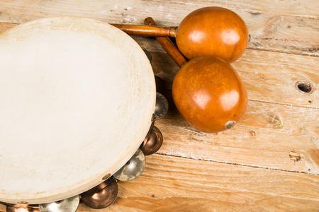 pandero: Pandereta y maracas en una mesa de madera Foto de archivo