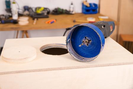 making hole: Hole saw resting on a half finished cajon flamenco percussion instrument