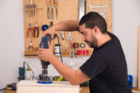 Artisan using a hole saw while crafting a cajon flamenco percussion instrument