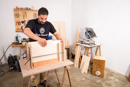 Artisan in his workshop assembling a cajon, a flamenco percussion instrument