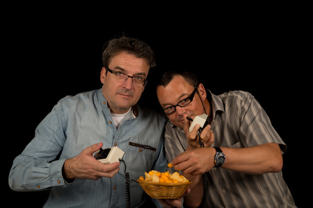 Two guys playing with a retro video game while tucking into snacks