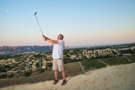 narcissist: Guy with selfie stick taking a self portrait outdoors Stock Photo
