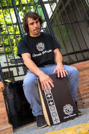 percussionist: Flamenco percussionist playing a cajon in an Andalusian street stetting. Editorial