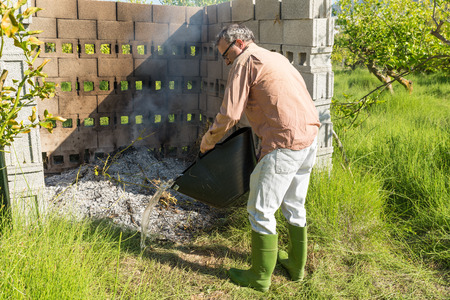 waste prevention: Farmer putting out an agricultural fire in a citrus plantation
