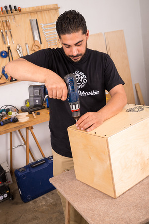 tightening: Artisan tightening the lid on a cajon flamenco percussion instrument