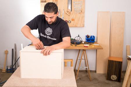 percussion instrument: Artisan working on a cajon flamenco percussion instrument Stock Photo