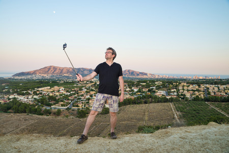 narcissist: Guy with selfie stick trying to look cool Stock Photo