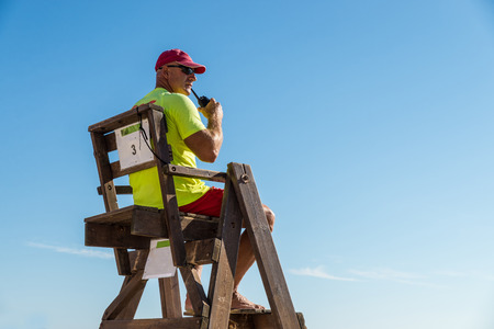 baywatch: Lifeguard sitting high up on his chair watching the beach Stock Photo