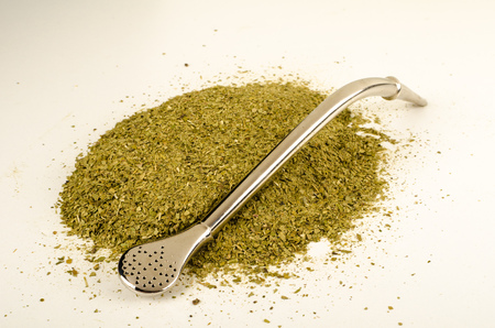 mate: Heap of mate herb with traditional  steel drinking straw Stock Photo