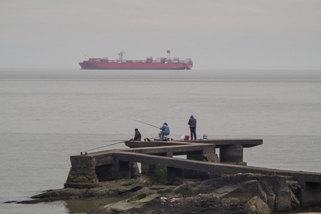 harbors: MONTEVIDEO, URUGUAY, JULY18, 2015: People fishing on Rio de la Plata while a large container ship sails by. Montevideo is on of South Americas  major harbors Editorial