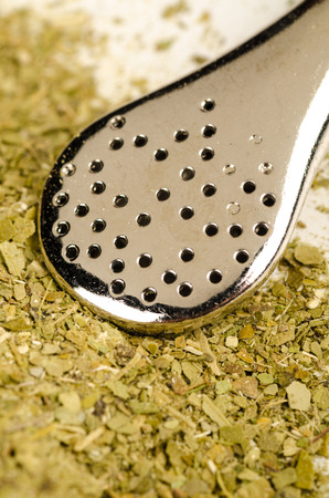 mate infusion: Heap of mate herb with traditional  steel drinking straw Stock Photo