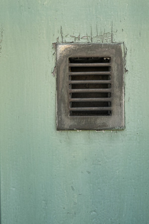 embedded: Old ventilation grid embedded in a wooden door