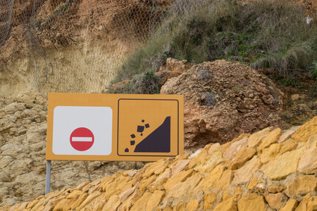 unstable: Sign warning sign against the backround on an unstable limestone cliff