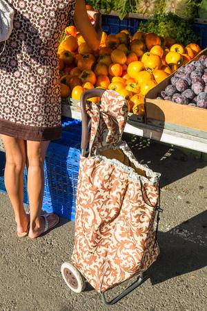 pull along: Woman choosing fresh produce on a street market stall Stock Photo
