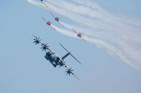 escorted: SAN JAVIER, SPAIN, OCTOBER18, 2015: Airbus A400M airlifter escorted by Sains Patulla Aguila squad on their  30th anniversary celebration event.