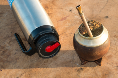 mate infusion: Traditional mate drinking equipment on a rustic table