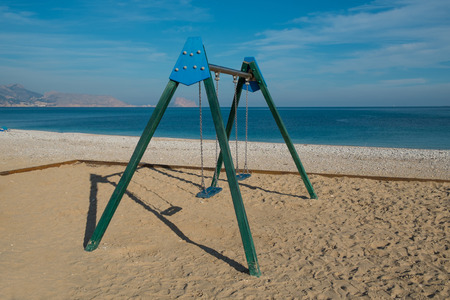 swing set: Swing set on a sunny Mediterranean resort beach