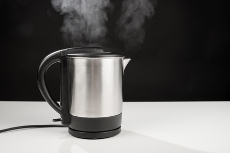 teakettle: Hot boiling kettle letting out some steam