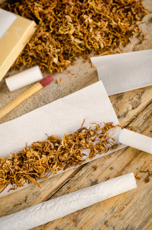 rolling paper: Accesories for rolling and smoking cigarettes on a rustic wooden table