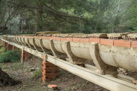 treed: Small agricultural aqueduct running across olive treed  farmland Stock Photo
