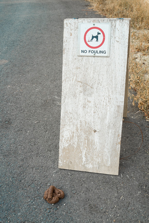 excrement: Dog excrement near a no fouling sign