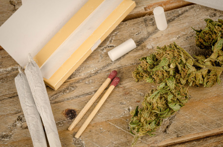 spliff: Ingredients to roll a joint on a rustic wooden table