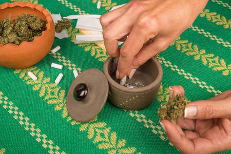 marihuana: Female hand holding a lit marihuana joint