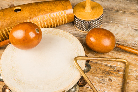 triangle musical instrument: Traditional small percussion instruments in a still life on a rustic wooden surface