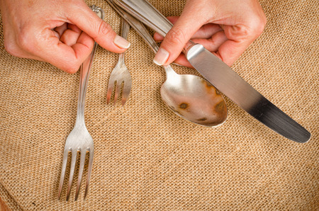 blotched: Female hands holding stained silverware in dear need for a polish
