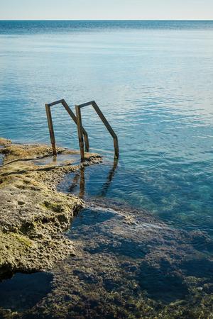seawater: Ladder in a natural seawater pool on a Mediterranean beach resort Stock Photo