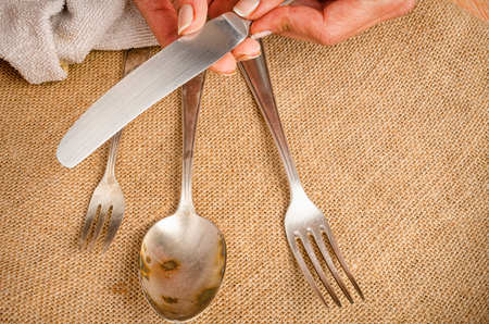 hand rubbing: Female hands cleaning spotty silverware with a cleaning product and a cloth