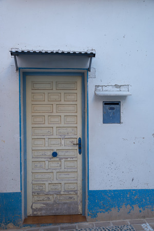 whitewashed: Old whitewashed Mediterranean village facade with a weathered wooden door