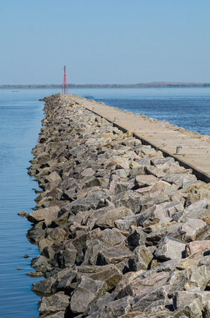 large rock: Large rock breakwater with a red beacon on its tip