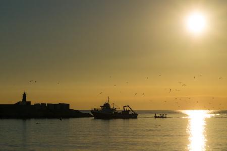 trawler: Trawler arriving to harbor at sunrise