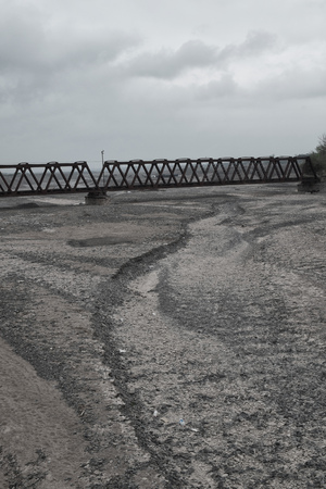 river bed: Dry rocky river bed crossed by an industrial bridge