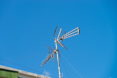 tv antenna: Rooftop tv antenna against blue sky Stock Photo