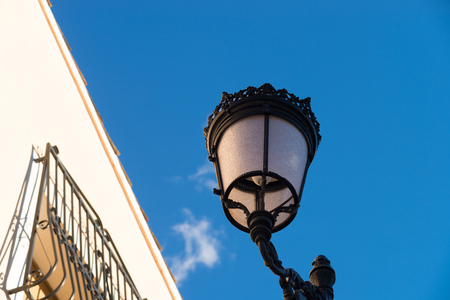 cast iron: Old cast iron street lamp against blue sky