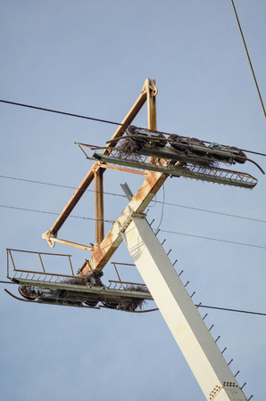 weathered: Somewhat weathered and rusty cableway pylon