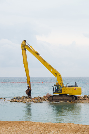 diggers: Large diggers working on a coastal dam Stock Photo