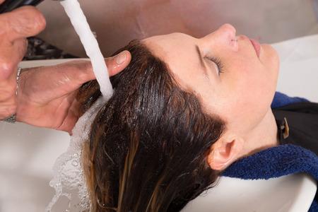 hair stylist: Hair stylist rinsing female customer hair after washing