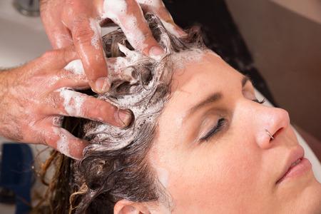 Hair stylist shampooing hair of a female customer