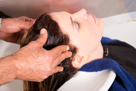 hair stylist: Hair stylist massaging clients head after washing and rinsing