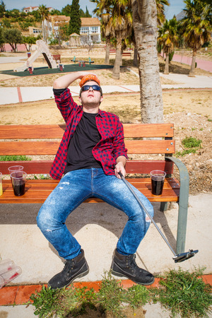 drunkard: Guy documenting his hangover on a park bench with a selfie, a concept