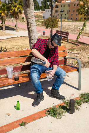 heavily: Guy getting heavily drunk on a park bench